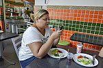 Mulher ao celular enquanto come.