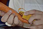 Pessoa descascando cenoura.